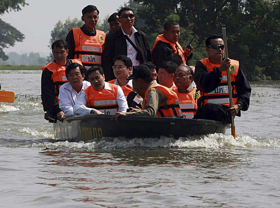 Thailand's Prime Minister Abhisit Vejjajiva, left front row, joins other officials to inspect the flood in Lop Buri province, central Thailand Thursday, Oct. 21, 2010. In Thailand, floods have killed nine people since the weekend. Runoff of those waters were due to sweep down the Chao Phraya river into the capital, Bangkok, late Wednesday. Photo: Str, AP