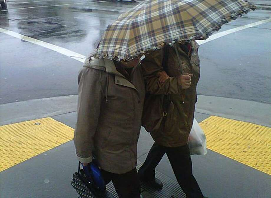 Two pedestrians cross Geary Street in the Richmond District of San Francisco during a light rainfall on Friday morning, October 22, 2010. Photo: Douglas Zimmerman, Courtesy To The SF Gate