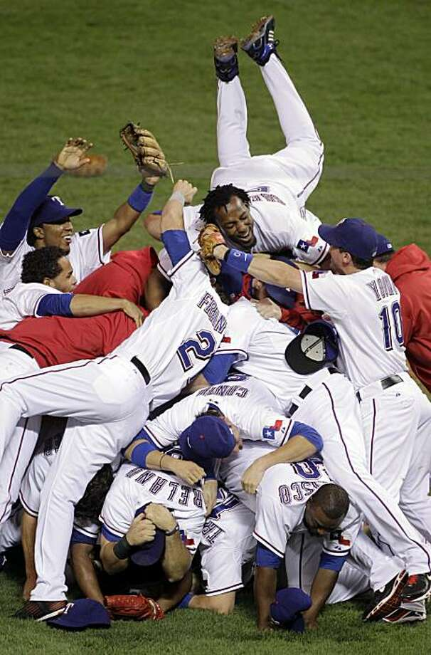 Texas Rangers' Vladimir Guerrero leaps on his teammates after the Rangers advanced to the World Series with a 6-1 win over the New York Yankees in Game 6 of baseball's American League Championship Series Friday, Oct. 22, 2010, in Arlington, Texas. Photo: Paul Sancya, AP