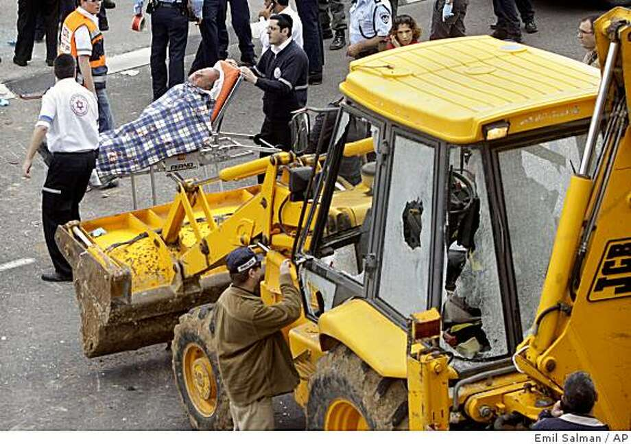 Israeli rescue workers evacuate an injured man next to a construction vehicle whose driver carried out an attack in Jerusalem, Thursday, March 5, 2009. A Palestinian driver rammed a large construction vehicle into a bus and police car on a Jerusalem highway Thursday, wounding two officers before he was shot and killed, the latest in a string of attacks by Palestinian militants using heavy machinery against Israeli targets.  (AP Photo/Jini, Emil Salman) ** ISRAEL OUT ** Photo: Emil Salman, AP