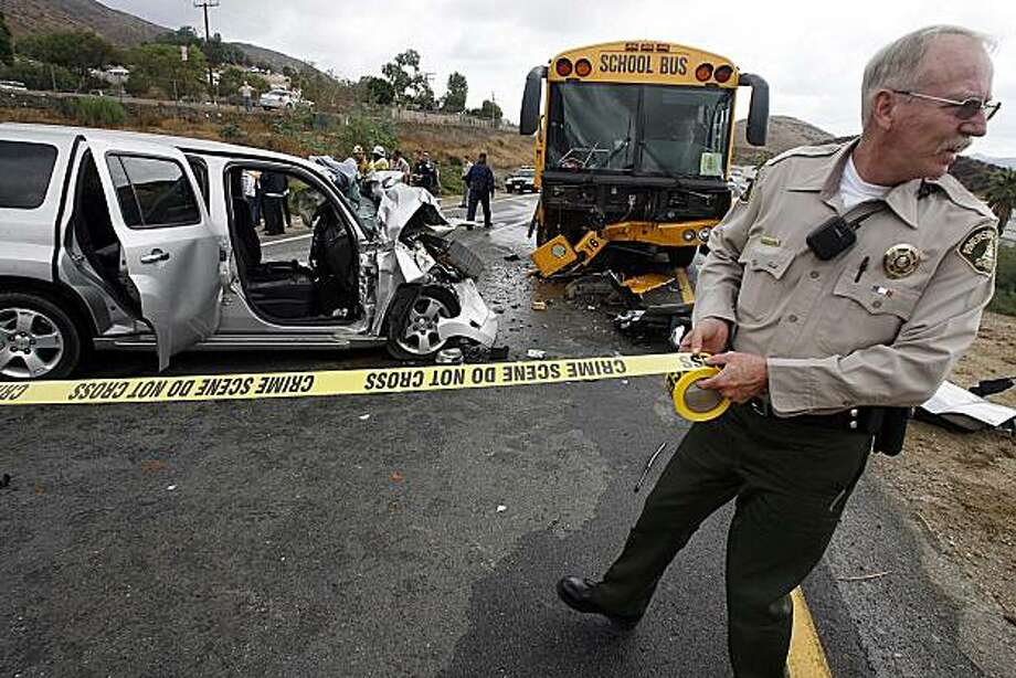 A California Highway Patrol officer tapes off the area around the site where a vehicle crashed into a school bus filled with Nueva Vista High School students  in Pedley, Calif., on Wednesday, Oct. 20, 2010. Photo: Silvia Flores, AP