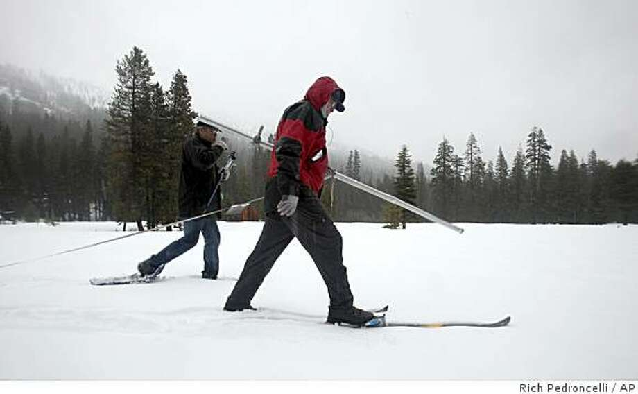 Frank Gehrke, chief of the snow surveys for the Department of Water Resources, carries a snow pack measuring pole as he and Alan Flint, a hydrologist for the United States Geological Service, walk through a snow covered field while conducting the snow pack survey near Echo Summit, Calif., Monday, March 2, 2009.  The survey found the snow pack 54 inches deep, with a water content of 25 inches, for an average of 101 percent for this location at this time of the year.(AP Photo/Rich Pedroncelli) Photo: Rich Pedroncelli, AP