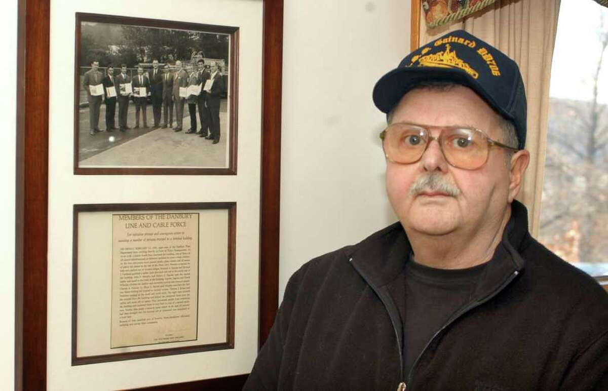 Retired telephone company lineman Robert Ingram with a framed photograph of the members of his SNET crew that rushed into the bomb-shattered Danbury police station on Feb. 13, 1970 to help victims of the explosion set off by brothers James and John Pardue to cover a robbery at the Union Savings Bank.