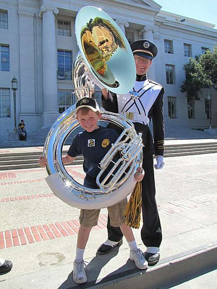 Cal band player Nathaniel Wagner lets Max Parry, son  of a Cal alumna, try on his tuba for size. Photo: Abby Bleistein