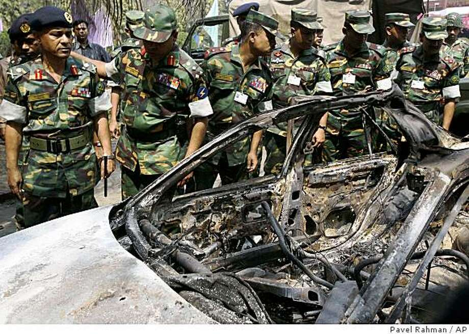 Bangladesh's army investigation committee chief Lt. General Mohammad Jahangir Alam Choudhury, left, and other members inspect a burned car at the Bangladesh Rifles headquarters in Dhaka, Bangladesh, Tuesday, March 3, 2009. (AP Photo/Pavel Rahman) Photo: Pavel Rahman, AP