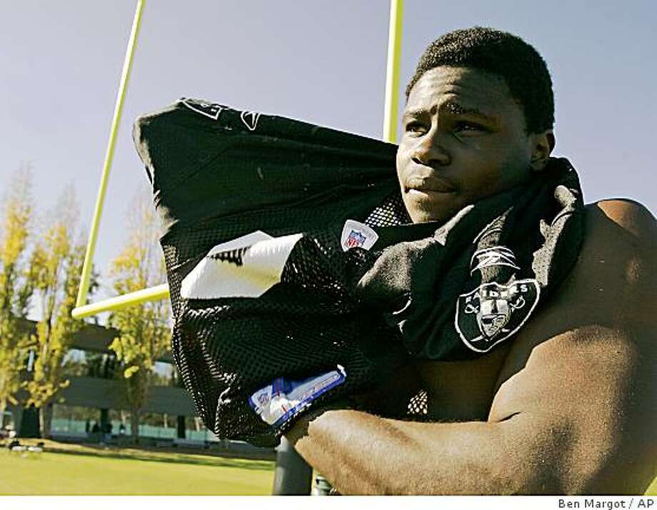 """Oakland Raider Isaiah Ekejiuba puts on a Raiders jersey following practice Thursday, Nov. 17, 2005, in Alameda, Calif. Ekejiuba played soccer as a boy in his native Nigeria, football was foreign to him; an American game he knew little about. Three years ago, an advertisement in the student newspaper about football tryouts at Virginia called out to Ekejiuba. There began his unlikely road to the NFL. """"A little back door into football,"""" Ekejiuba says with his friendly smile, sitting in the Raiders' locker room before a recent practice. (AP Photo/Ben Margot) Photo: Ben Margot, AP"""
