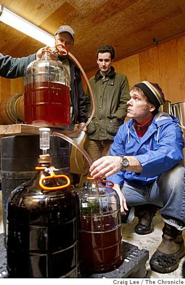 Student, Joe Shotwell (right), topping off a carboy of wine during the winemaking class at Napa Valley College in Napa, Calif., on February 17, 2009. The two students in the back are, Mark Buckley (left, ball cap), and James Russell (middle). Photo: Craig Lee, The Chronicle