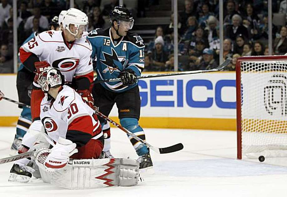 San Jose Sharks center Patrick Marleau, right, redirects the puck for a goal past Carolina Hurricanes goalie Cam Ward (30) and defenseman Joni Pitkanen (25), of Finland, during the second period of an NHL hockey game Tuesday, Oct. 19, 2010, in San Jose, Calif. Photo: Tony Avelar, AP