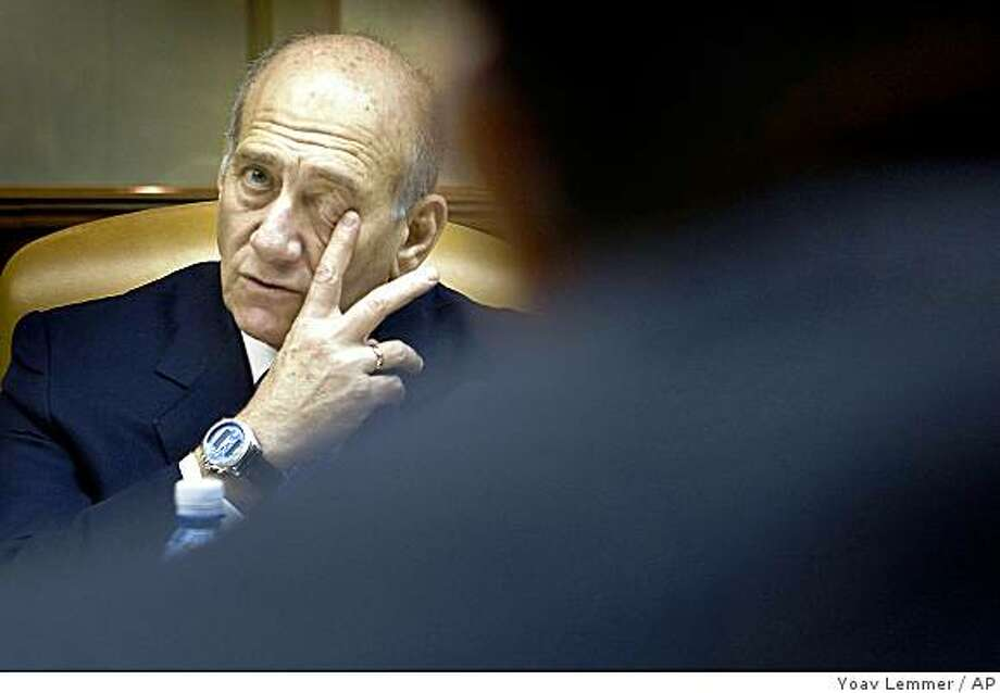 """Outgoing Israeli Prime Minister Ehud Olmert attends the weekly cabinet meeting in Jerusalem, Sunday, March 1, 2009. Olmert threatened """"uncompromising"""" retaliation against Gaza militants Sunday as the country's leadership met, six weeks after halting a military offensive meant to end Palestinian rocket fire, to decide how to respond now that it appears clear that goal was not achieved. (AP Photo/Yoav Lemmer, Pool) Photo: Yoav Lemmer, AP"""