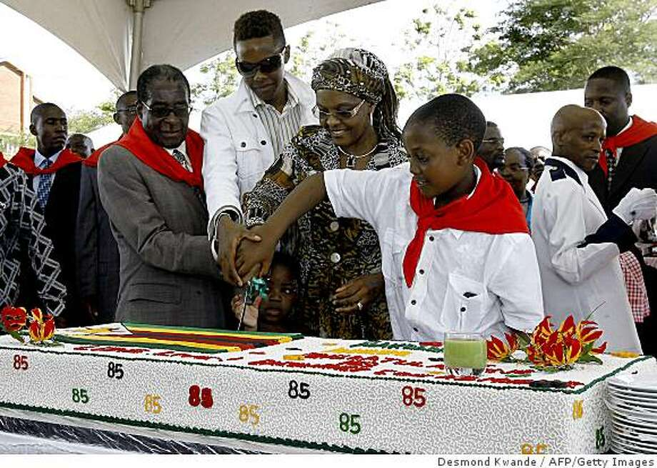 Zimbabwean President Robert Mugabe (L), his wife Grace (Centre R), his son Robert Junior Mugabe (Centre L) and his youngest son Chatunga Mugabe (R) cut his birthday cake in Chinhoyi 115km from Harare on February 28, 2009 during the celebrations for the Mugabe's 85th birthday. Mugabe turned 85 on February 21. AFP PHOTO/Desmond Kwande (Photo credit should read DESMOND KWANDE/AFP/Getty Images) Photo: Desmond Kwande, AFP/Getty Images