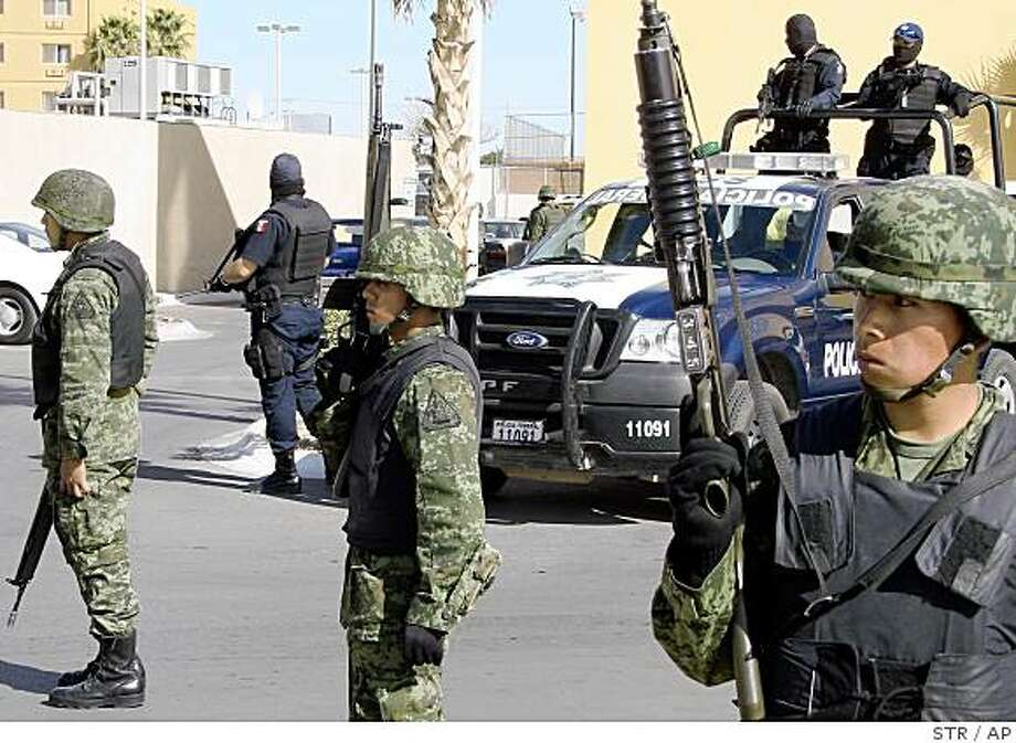 Mexican army soldiers and federal police guard the perimeter around the site where the Interior secretary and members of the federal security cabinet are gathered to discuss the ongoing wave of violence in the border state of Chihuahua, in Ciudad Juarez, Mexico Wednesday, Feb. 25, 2009. After the meeting, federal authorities announced that police and army reinforcements will be sent to the state of Chihuahua to help battle organized crime gangs. (AP Photo) Photo: STR, AP