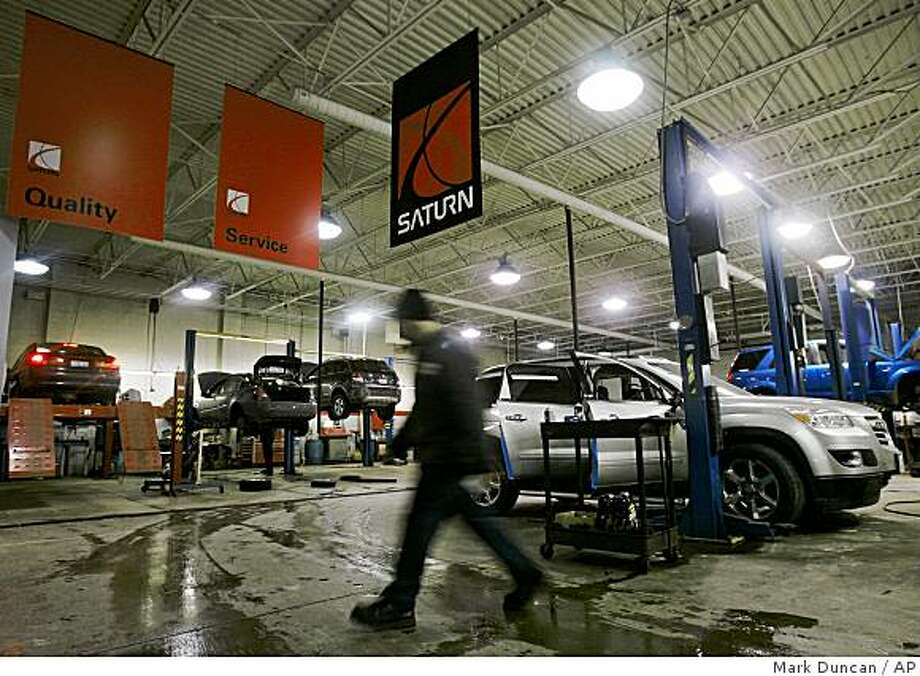 A mechanic walks through service area at Saturn of North Olmsted in North Olmsted, Ohio, Friday, Feb. 20, 2009. The last hope to stop General Motors Corp.'s wounded Saturn brand from falling out of the solar system appears to rest with some unknown automaker building cars for the dealers to sell.  (AP Photo/Mark Duncan) Photo: Mark Duncan, AP