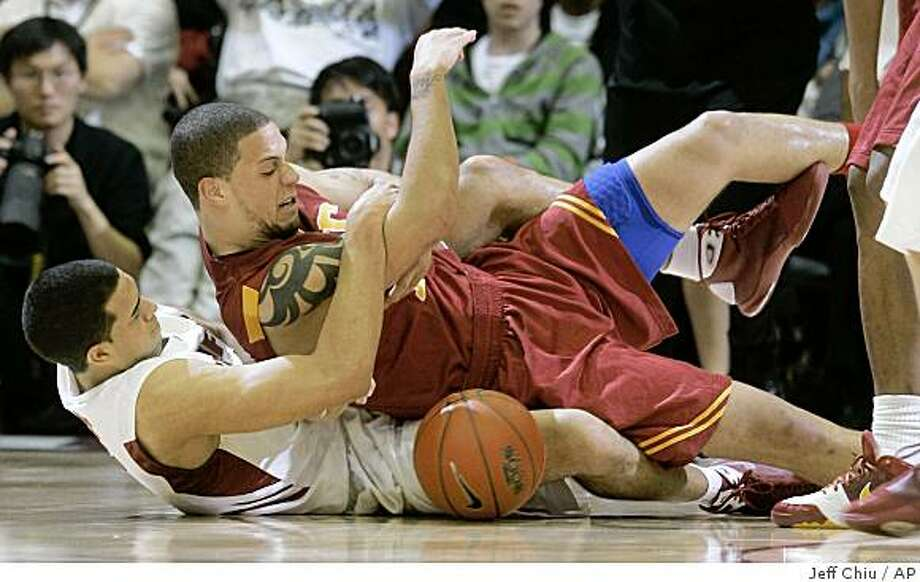 Stanford's Landry Fields, bottom, and Southern Cailfornia's Daniel Hackett wrestle for a loose ball in the first half of an NCAA college basketball game in Stanford, Calif., Saturday, Feb. 28, 2009. (AP Photo/Jeff Chiu) Photo: Jeff Chiu, AP