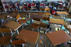 In this June 19, 2011 file photo, children's desks, backpacks, and school supplies lie abandoned inside an earthquake-rattled primary school classroom in Namie, Japan. The photo was one in a series of 12 which won the 3rd place prize in the General News Stories category of the 2012 World Press Photo contest.  (AP Photo/David Guttenfelder for National Geographic Magazine, File)