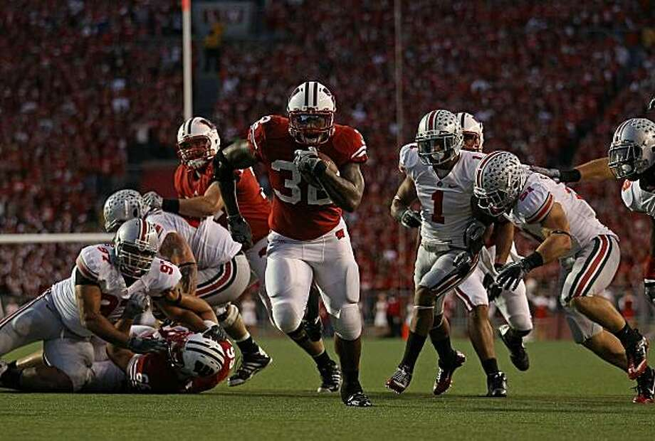 MADISON, WI - OCTOBER 16: John Clay #32 of the Wisconsin Badgers runs past Ross Homan #51 and Devon Torrence #1 of the Ohio State Buckeyes for a touchdown at Camp Randall Stadium on October 16, 2010 in Madison, Wisconsin. Photo: Jonathan Daniel, Getty Images