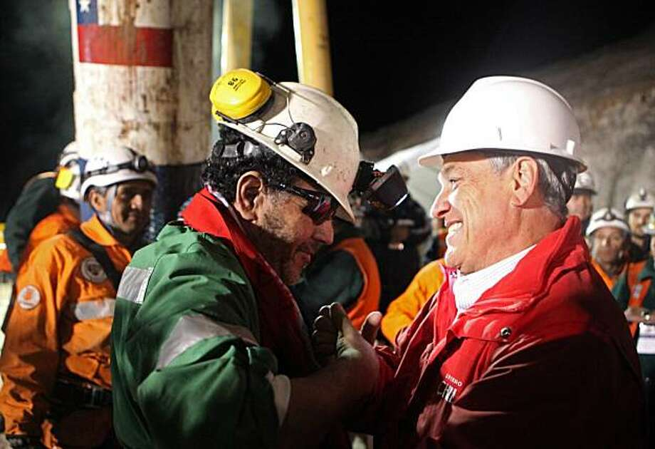 FOR EDITORIAL USE ONLY - In this photo released by the Chilean Government, the last miner to be rescued, Luis Urzua, left, shakes hands with Chile's President Sebastian Pinera after being freed from the collapsed San Jose gold and copper mine where he hadbeen trapped with 32 other miners for over two months near Copiapo, Chile, Wednesday Oct. 13, 2010. The 69-day underground ordeal reached its end Wednesday night after 33 trapped miners were hauled up in a cage through a narrow hole drilled through 2,000feet (700 meters) of rock. Photo: Hugo Infante, AP