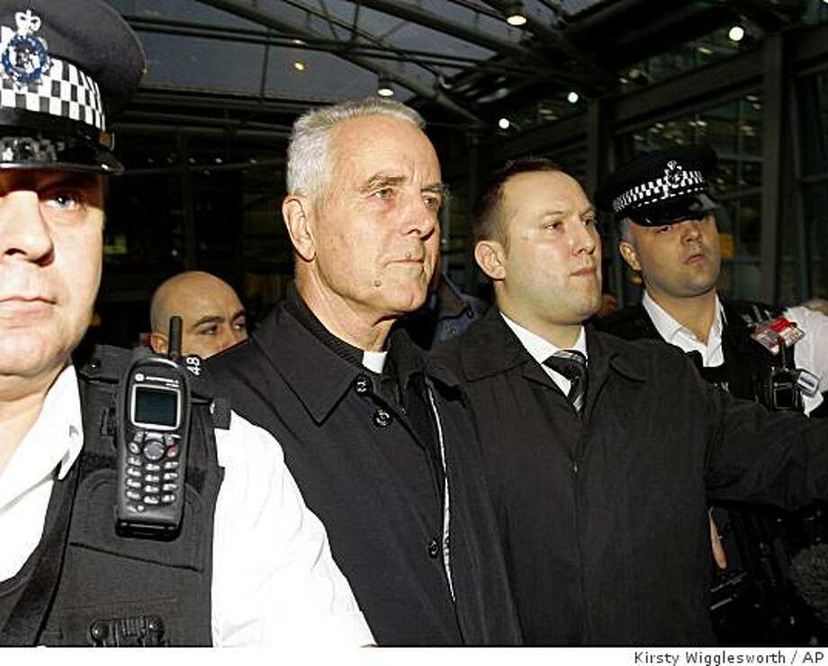 "Bishop Richard Williamson, second from left in foreground, is escorted out of Heathrow airport by police and security officers after arriving on a flight from Argentina, in London, Wednesday, Feb. 25, 2009. Argentina's government on Thursday ordered the traditionalist Catholic bishop to leave the country or face expulsion, citing his failure to declare a job change as required by immigration law as well as his denials of the Holocaust, which it called ""an insult"" to humanity. (AP Photo/Kirsty Wigglesworth) Photo: Kirsty Wigglesworth, AP"