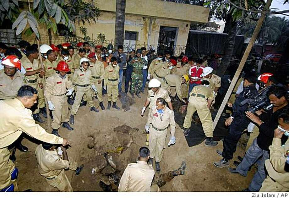 Bangladesh's firefighters dig out the bodies of army officers from shallow holes inside the Bangladesh Rifles headquarters in Dhaka, Bangladesh, Friday, Feb. 27, 2009. Security forces searching the headquarters of a mutinous Bangladeshi border guard unit on Friday discovered the bodies of dozens of officers in shallow graves on the compound, raising the death toll to 66, officials said. (AP Photo/Zia Islam) Photo: Zia Islam, AP