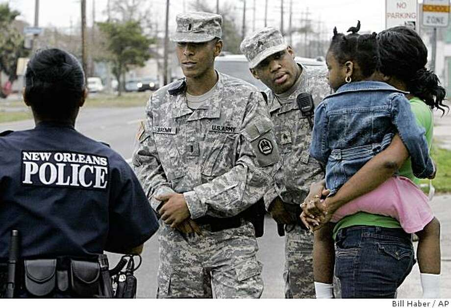 Louisiana National Guard Lt. Ronald Brown, Jr., center, and Sgt. Wayne Lewis  talk with a New Orleans police officer after arriving at a domestic dispute call in the 9th Ward of New Orleans, Thursday, Feb. 26, 2009. The Last members of the Louisiana National Guard, which came to town after Hurricane Katrina in August of 2005, are pulling out Sunday March 1, 2009. Photo: Bill Haber, AP