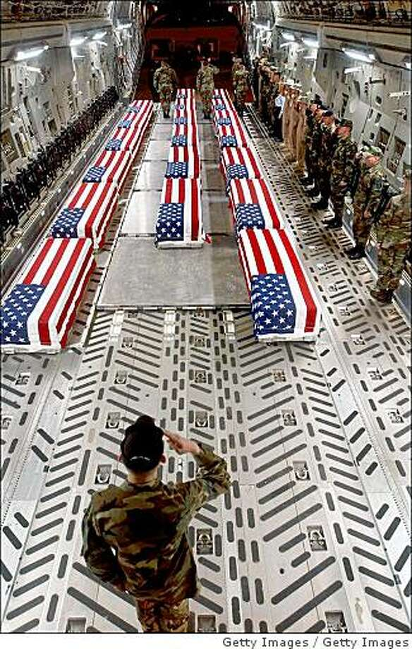 UNDATED - (FILE PHOTO)  This undated handout photo originally provided by the U.S. Air Force and posted on www.thememoryhole.org, shows flag-draped coffins of U.S. casualties from Iraq being offloaded by a military honor guard from a cargo plane in Dover, Delaware. U.S. Defense Secretary Robert Gates announced February 26, 2009 that the family's of U.S. war dead will be able to decide whether their loved one's casket can be photographed by the media upon the arrival at Dover Air Force base in Deleware. A ban has been in place since 1991.  (Photo by Thememoryhole.org via Getty Images) Photo: Getty Images
