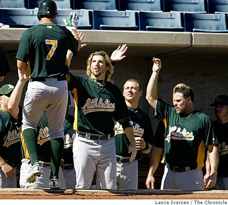 Bobby Crosby is greeted when he returned to the dugout after hitting a solo home run. Oakland Athletics played their first Spring Training game with the Milwaukee Brewers at Maryvale Baseball Park in Phoenix Arizona Wednesday February 25, 2009. Photo: Lance Iversen, The Chronicle