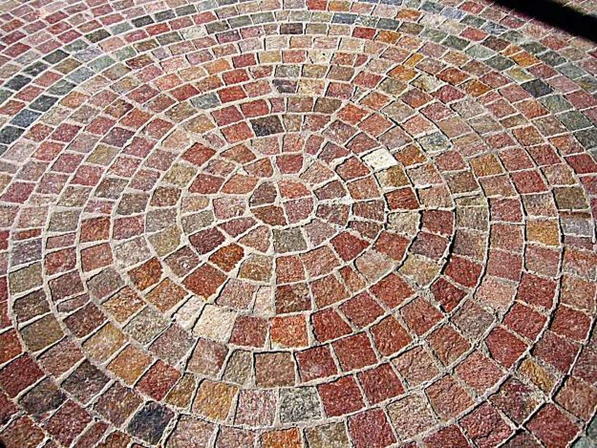 Prophyry pavers. Essentially a fast-cooled magma, porphyry is denser than most granite and absorbs little water or oil that might break it down.