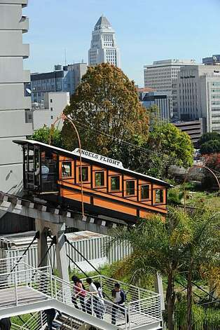 "People walk uphill as the Angels Flight Railway, for the first time in more than nine years, resumes ferrying passengers up and down Bunker Hill in downtown Los Angeles March, 15, 2010.  Angel's Flight, which has been dubbed ""the shortest railway in the world,"" was shut down in 2001 after a fatal accident. The funicular was opened in 1901 to take passengers on the one-minute trip up and down Bunker Hill, initially for a penny. The fare is now 25 cents and the train still features the original cars from 1901. Photo: ., AFP/Getty Images"