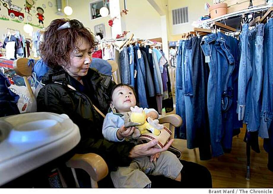 "Yumi Fujimoto holds her grandson Rai while Yumi's daughter does some shopping at Lovely Bump at 509 San Mateo Avenue. San Mateo Avenue in San Bruno is called ""The Avenue"" in one section, a collection of unique shops that make up a real Bay Area main street. Photo: Brant Ward, The Chronicle"