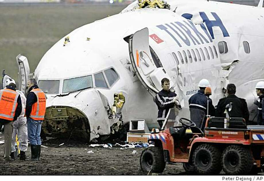 Rescue workers are seen near the wreckage of a Turkish Airlines aeroplane at Amsterdam's Schiphol Airport Wednesday, Feb. 25, 2009.   The aeroplane, with 135 people aboard, slammed into a muddy field while attempting to land at Amsterdam's main airport.  Nine people were killed and more than 50 were injured, many seriously, officials said.  The Boeing 737-800 broke into three pieces on impact about two miles (three kilometers) short of a runway.  (AP Photo / Peter Dejong) Photo: Peter Dejong, AP