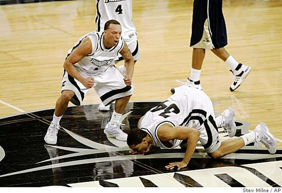 Providence's Jeff Xavier, left, and Jonathan Kale, kissing floor, celebrate after defeating No. 1 Pittsburgh 81-73 in a game Tuesday, Feb. 24, 2009, in Providence, R.I. Photo: Stew Milne, AP