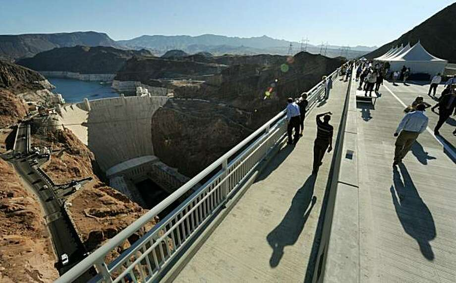 Locals walk across the newly opened Mike O'Callaghan-Pat Tillman Memorial Bridge which spans the Colorado River, beside the Hoover Dam on the border of Arizona and Nevada, October 14, 2010. Construction on the nearly 2,000-foot-long (609-foot) bridge began in late January 2005 and the bridge spans the Black Canyon (south of the Hoover Dam) and rises nearly 900 feet (274 meters) above the Colorado River. As a consequence of the heightened security following the September 11, 2001 attacks, truck traffic over the Hoover Dam had been banned, in an effort to safeguard the dam from hazardous spills or explosions. However this has not eliminated the threat of a possible attack on the dam, as regular traffic still passes over it and the new bypass bridge will r Photo: Mark Ralston, AFP/Getty Images