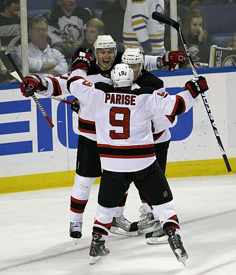 New Jersey Devils' Ilya Kovalchuk, back, of Russia, celebrates his overtime goal with Matt Taormina, center, and Zach Parise, front, during an NHL hockey game in Buffalo, N.Y., Wednesday, Oct. 13, 2010. The Devils defeated the Buffalo Sabres 1-0. Photo: David Duprey, AP