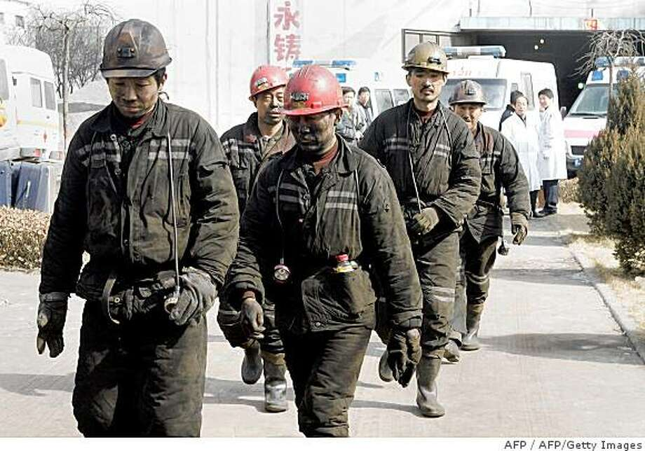 Chinese miners make their way out from the Tunlan Coal Mine in Gujiao, in northern China's Shanxi province on February 22, 2009.  Seventy-four workers were confirmed dead and dozens trapped underground after a gas blast at a north Chinese colliery, the worst accident to hit the nation's mines in over 14 months.               CHINA OUT GETTY OUT        AFP PHOTO (Photo credit should read AFP/AFP/Getty Images) Photo: AFP, AFP/Getty Images