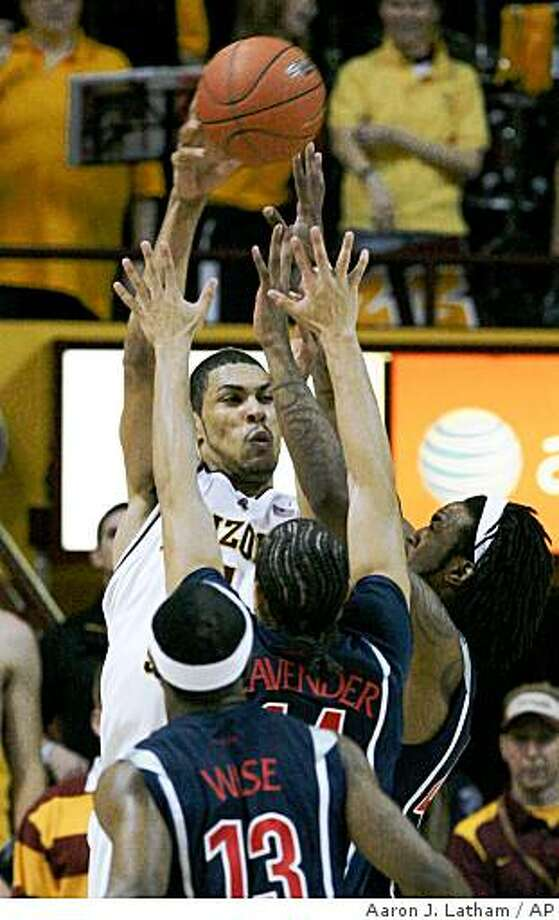 Arizona State's Jeff Pendergraph passes under pressure from Arizona's Jordan Hill, right, and Brendon Lavender during the first half of an NCAA college basketball game in Tempe, Ariz., Sunday, Feb. 22, 2009. (AP Photo/Aaron J. Latham) Photo: Aaron J. Latham, AP