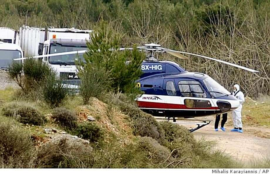 Police forensic experts investigate a helicopter used in the escape of convicts Vassilis Paleokostas and Alket Rizaj from Athens' high-security Korydallos prison, at a clearing north of Athens, Sunday, Feb. 22, 2009. Paleokostas and Rizaj both escaped from the same prison using the same means on June 4, 2006, but had been apprehended separately after committing more crimes. Police have mounted a search for the escapees. (AP Photo/PHASMA, Mihalis Karayiannis) ** GREECE OUT ** Photo: Mihalis Karayiannis, AP