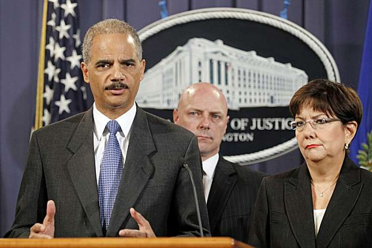 Attorney General Eric Holder, left, accompanied by US Attorney Rosa Emilia Rodriguez-Velez of the District of Puerto Rico, right, and FBI Executive Director Shawn Henry, answers questions during a news conference at the Justice Department in Washington, Wednesday, Oct. 6, 2010.