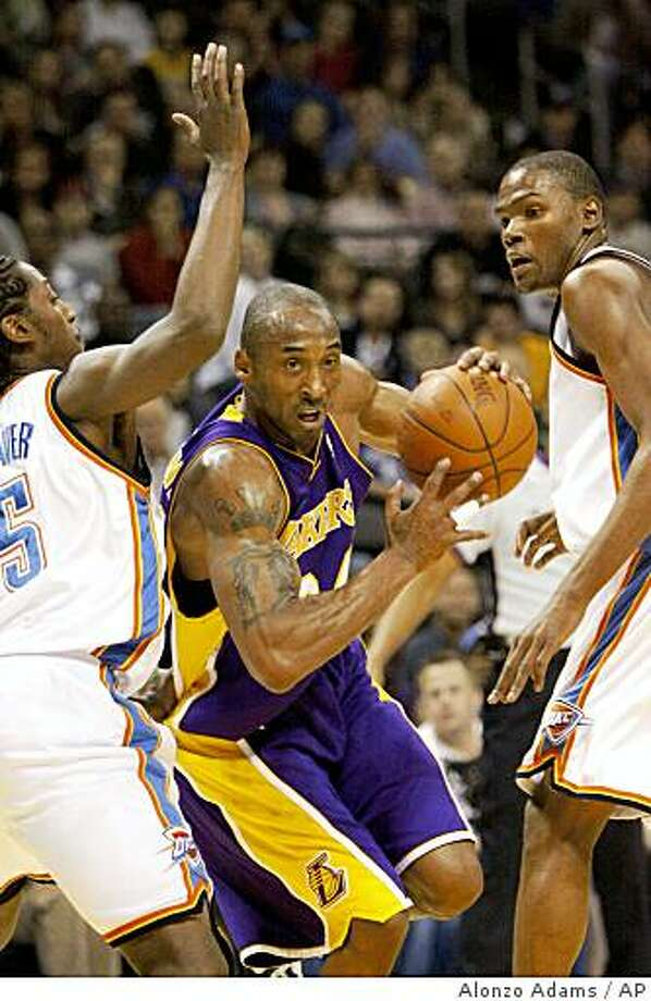 Los Angeles Lakers guard Kobe Bryant, center, drives to the basket between Oklahoma City Thunder's Kyle Weaver, left and Kevin Durant during the first half of an NBA basketball game in Oklahoma City, Tuesday, Feb. 24, 2009. (AP Photo/Alonzo Adams) Photo: Alonzo Adams, AP