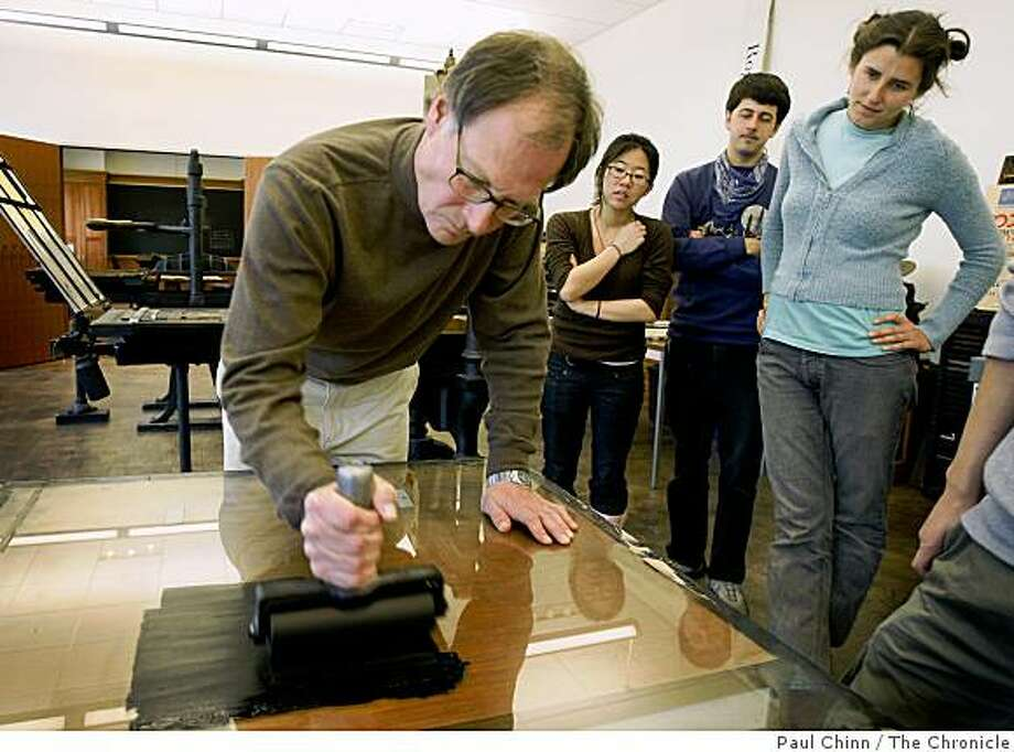 History teacher Les Ferriss spreads ink on a glass plate during a printing demonstration for students (L to R) Natalie Tsang, Matt Senate and Eleanor Warner during Ferriss' printing class at UC Berkeley in Berkeley, Calif., on Friday, Feb. 13, 2009. Photo: Paul Chinn, The Chronicle