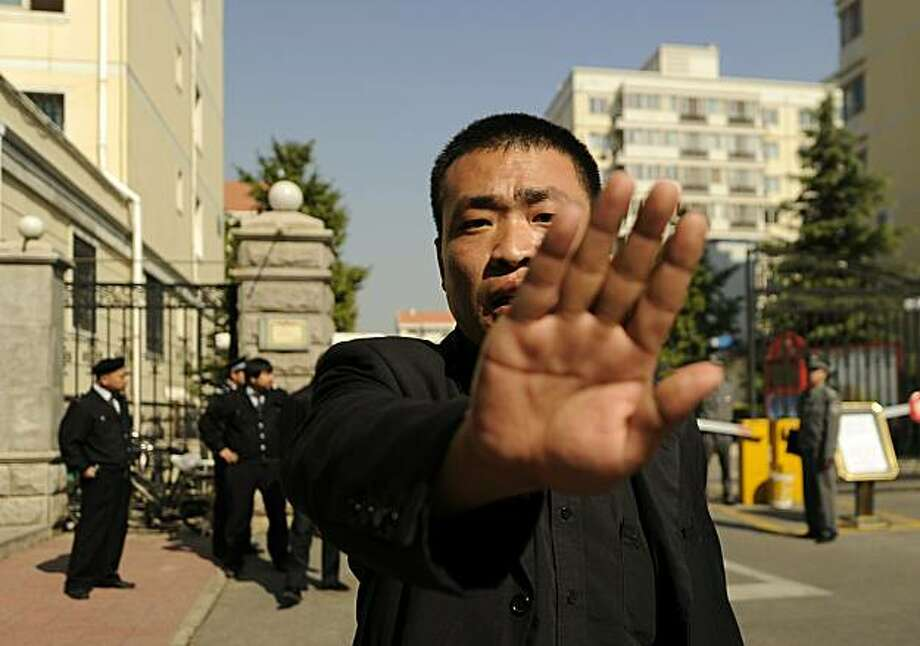 A plain-clothes policeman tries to stop photos being taken outside the house of the wife of jailed Chinese Nobel Peace laureate Liu Xiaobo in Beijing on October 13, 2010. Liu Xia said she was prevented from meeting with Norwegian diplomats as authoritieskept her under tight house arrest since the Nobel Committee in Oslo awarded this year's prize to her dissident husband for advocating political reform and respect for human rights in China. Photo: Peter Parks, AFP/Getty Images