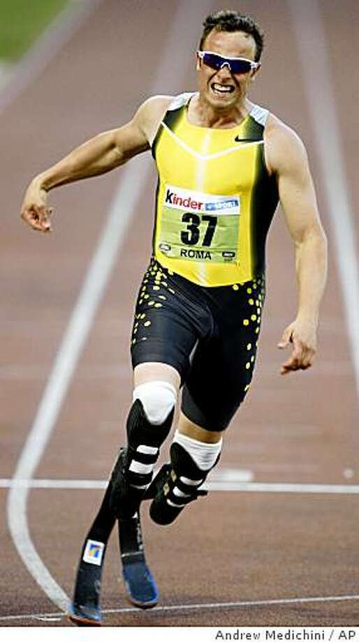 ** FILE **  IN a file photo South Africa's Oscar Pistorius crosses the finish line in the men's 400-meter race during the Golden Gala athletics meeting in Rome's Olympic stadium, Friday, July 13, 2007. Pistorius, who races on carbon fiber blades attached below his knees, placed second.  Track and field's ruling body postponed until Monday, Jan. 14, 2008,  its ruling whether double-amputee sprinter Pistorius would be eligible to race in the Olympics or whether his curved, prosthetic racing blades give him an unfair edge.   (AP Photo/Andrew Medichini) Photo: Andrew Medichini, AP