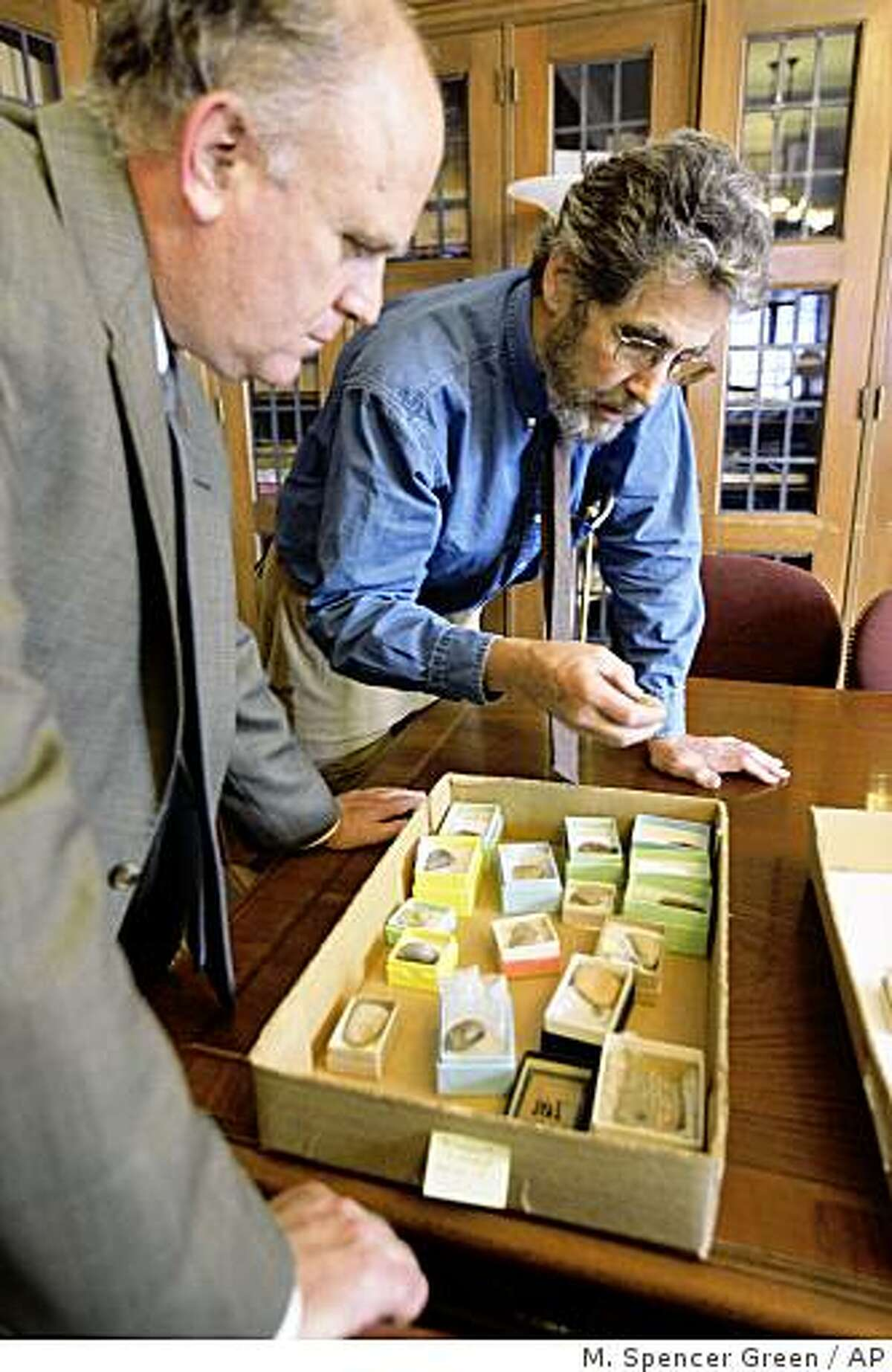 **ADVANCE FOR SUNDAY, FEB. 22** Gil Stein, director of the University of Chicago's Oriental Institute, left, and Matt Stolper, director of the Persepolis Fortification Archive, look over a selection of Aramaic tablets Oct. 16, 2008. The tablets are the subject of an unusual lawsuit. Victims of a terrorist bombing in Israel in 1997 won a multimillion judgment against Iran and are now trying to collect by seizing the tablets and selling them. (AP Photo/M. Spencer Green)