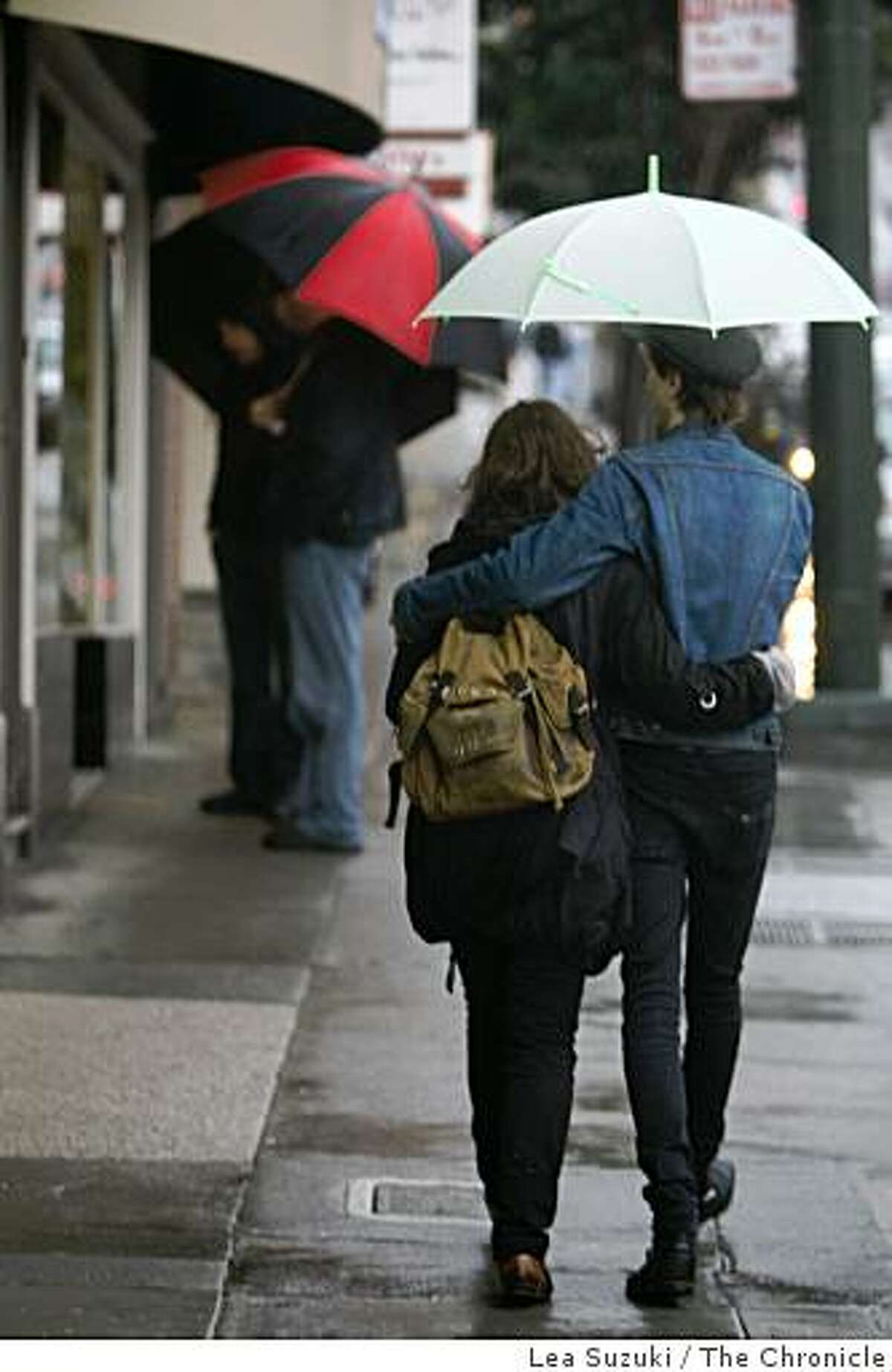 Victoria Sim ( to r) and Lynn Tolliver of Montreal, Canada share an umbrella as they walk in the rain on Castro Street in San Francisco, Calif. on Sunday, February 22, 2009.