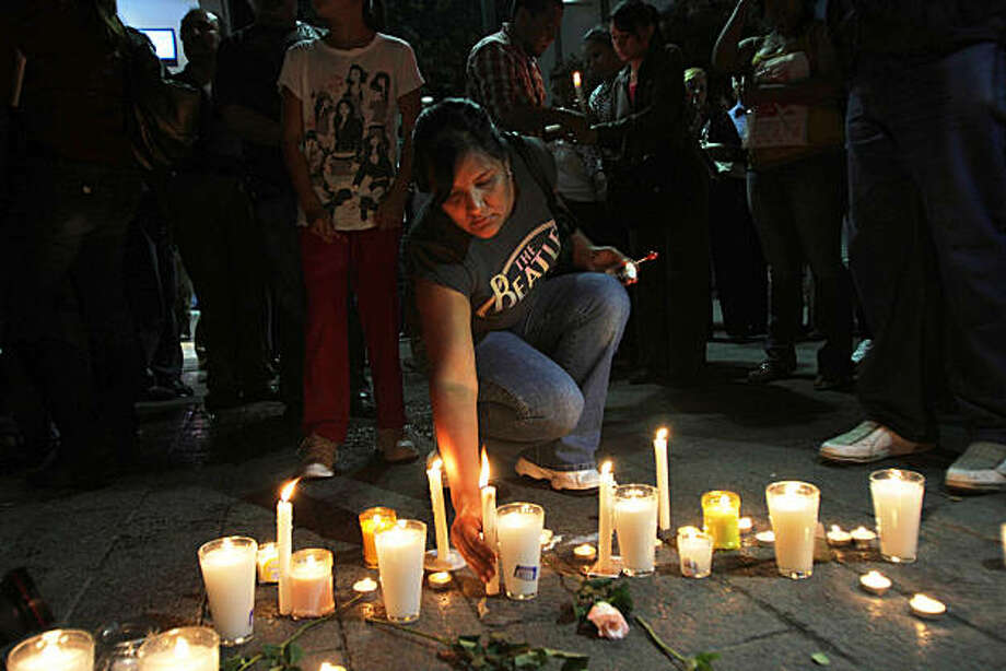A woman sets a candle at the site where college student Lucila Quintanilla was killed in Monterrey, Mexico, Thursday, Oct. 7, 2010. Quintanilla was shot to death accidentally Wednesday as she was walking in downtown Monterrey when unknown gunmen opened fire. Photo: Carlos Jasso, AP