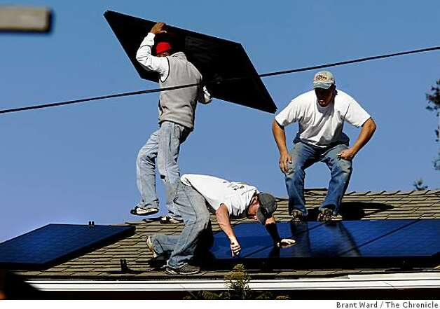 Solar installers Frank Teague (low with screwdriver) and Delmar Oliveira (right) put the panels in place. The solar industry has been a bright spot in a down economy. The Los Gatos based company Akeena Solar is installing 44 solar panels on a home in the Oakland hills Thursday January 15, 2008. Photo: Brant Ward, The Chronicle