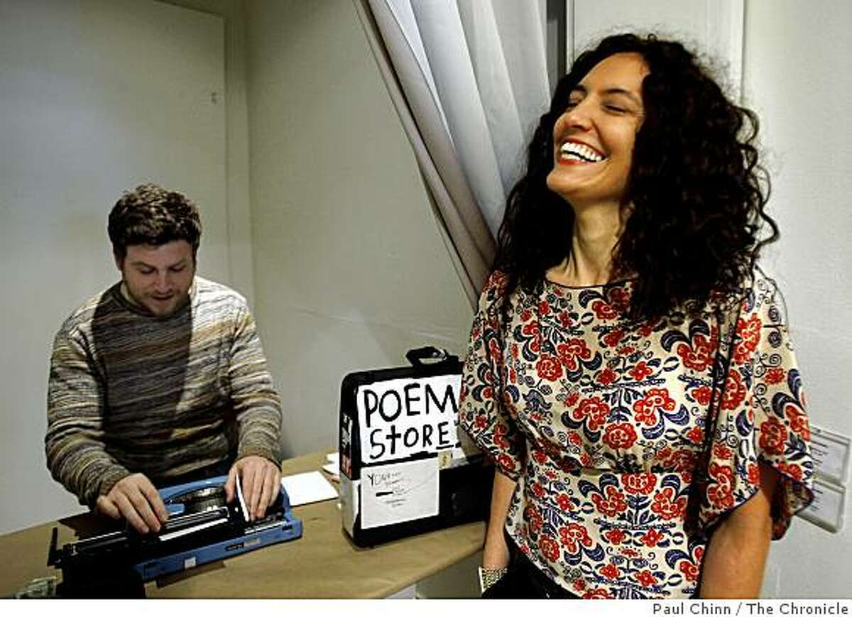 Gallery owner Kimberly Johansson (right) is amused by a poem written by artist/poet Zach Houston who brought his Poem Store to the Johansson Projects gallery in Oakland, Calif., on Saturday, Feb. 14, 2009. Houston bangs out his improvisational poetry on a manual typewriter and hands them out to his admirers.