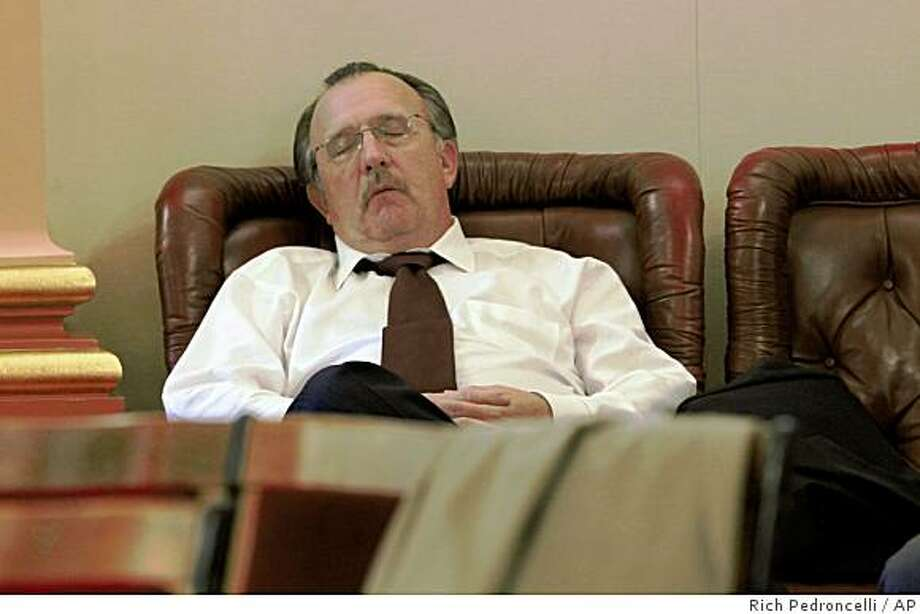 State Sen. Bob Dutton, R-Rancho Cucamonga, gets some sleep in the back of the state Senate Chambers in the early morning hours at the Capitol in Sacramento, Calif., Wednesday, Feb. 18, 2009. Senate President Pro Tem Darrell Steinberg, D-Sacramento, confined Senate members to the Capitol, overnight, in an attempt to coax one Republican to vote for the stalled state budget package.(AP Photo/Rich Pedroncelli) Photo: Rich Pedroncelli, AP