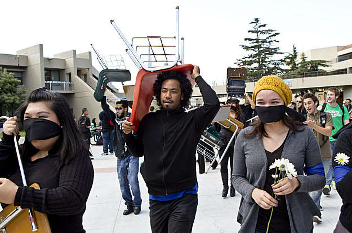 College of Alameda students carry classroom chairs through campus during a protest against budget cuts at the school in Alameda, Calif., on Thursday, October 7, 2010.