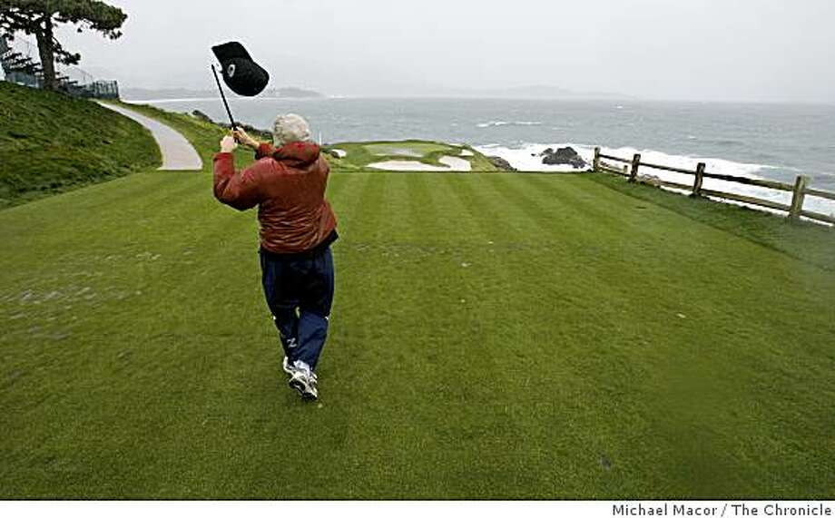 Chronicle columnist, Scott Ostler tees off on the par-3 7th hole at Pebble Beach, as the winds blows off his hat.  AT&T Pebble Beach National Pro-Am on Sunday Feb. 15, 2009, in Pebble Beach, Calif.  4th round was cancelled and rescheduled for tomorrow morning, due to heavy wind and rains. Photo: Michael Macor, The Chronicle
