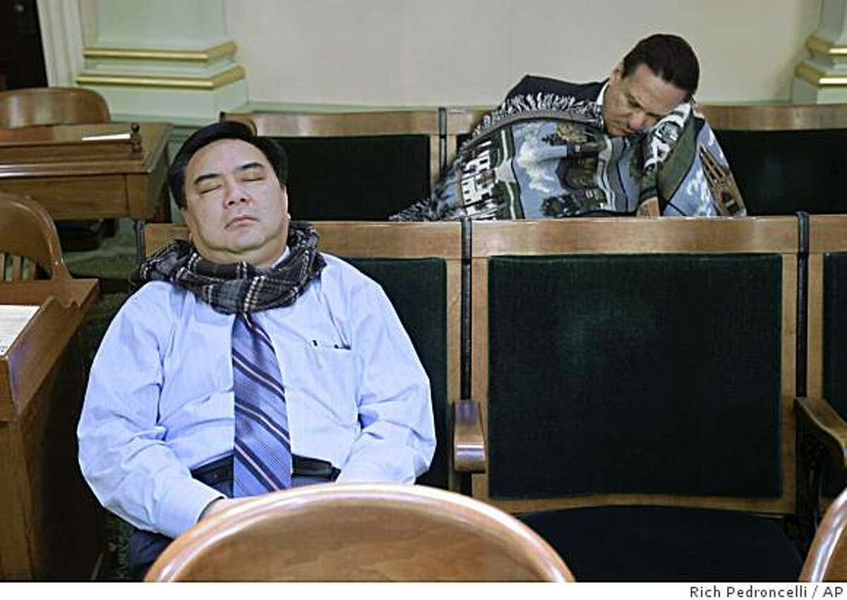 Assembly members Van Tran, R-Costa Mesa, left, and Joe Coto, D-San Jose, right, sleep in the back of the Assembly Chambers in the early morning hours at the Capitol in Sacramento, Calif., Sunday, Feb. 15, 2009. In an effort to get a state budget plan approved, Assembly Speaker Karen Bass, a Democrat, locked down her chamber about 3:30 a.m., forcing members to remain. (AP Photo/Rich Pedroncelli)