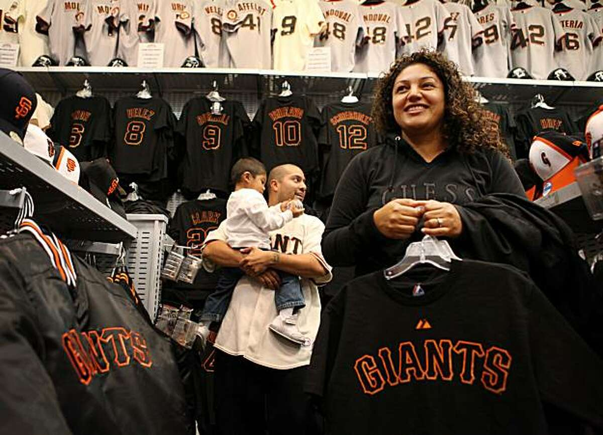 Armed with the excitement from the Giants recent victory and updated Giants gear, Angel Aquino and Carolina Aquino, with their son, Isaac Aquino, 2, head for the checkout at the Giants Dugout Store on Monday Oct. 4, 2010 in San Francisco, Calif.